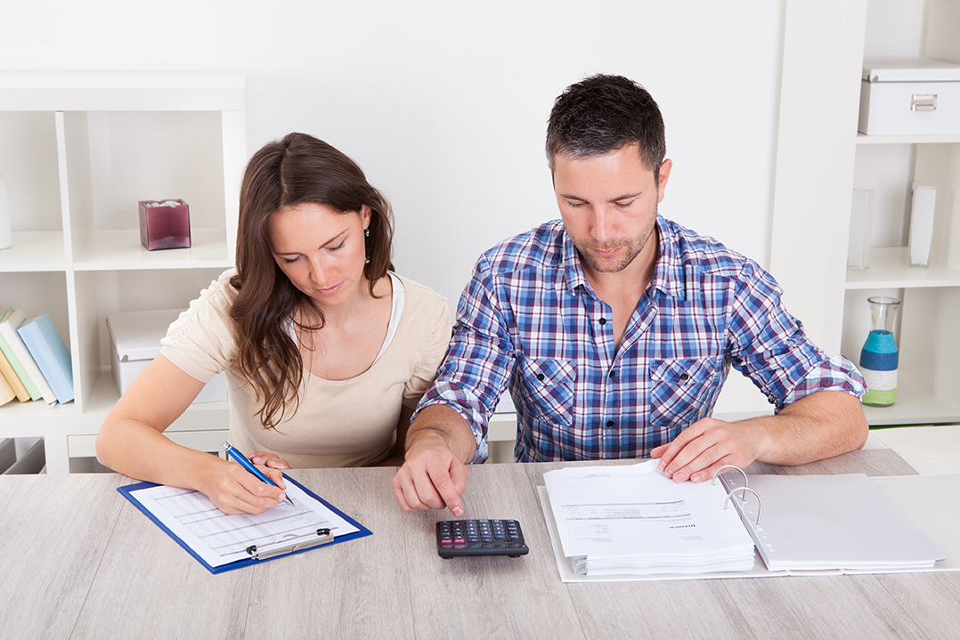 A man and woman sitting down going over forms and crunching numbers