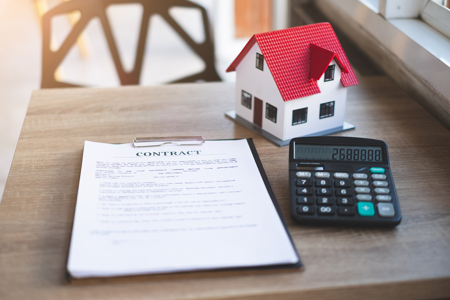 A model house, calculator, and a contract sitting on a table