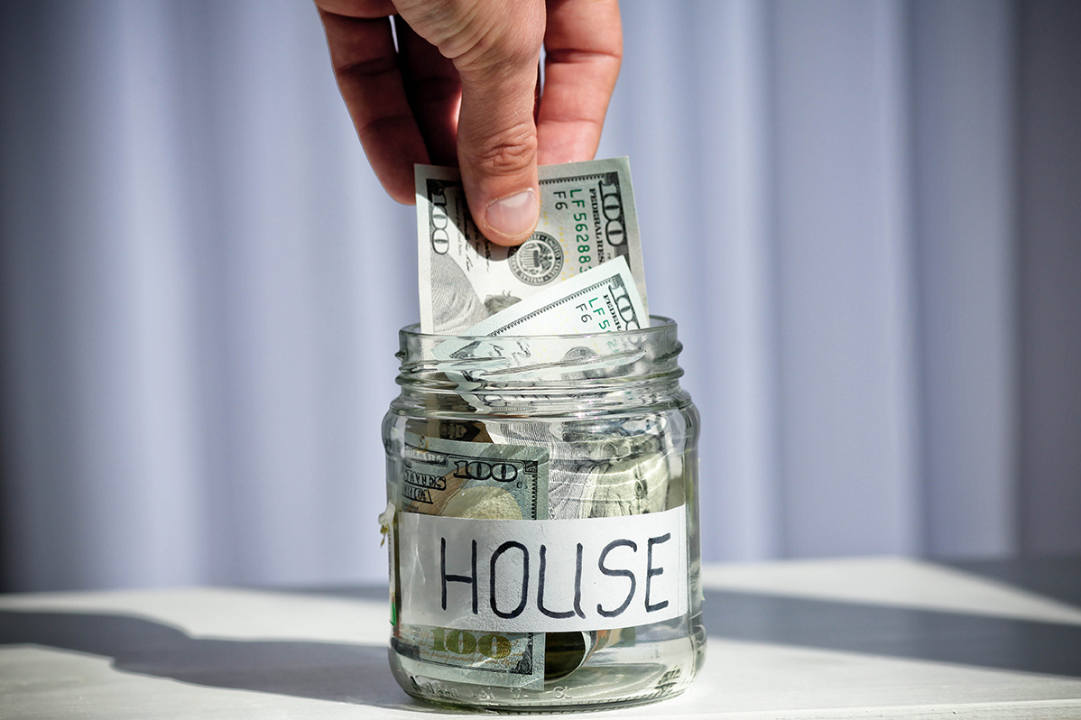 A hand putting a hundred dollar bill in a savings jar for a house